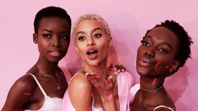 Three models with short curly and afro-textured hair blow petals at the camera for a Victoria