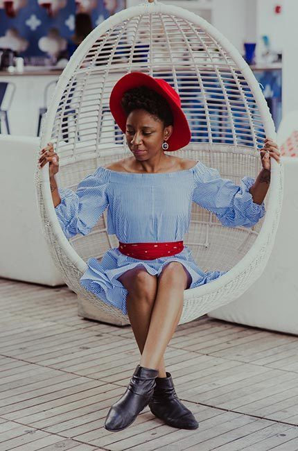African-American woman, sitting in oval swing chair, is dressed blue and white striped dress wears red wide-brimmed hat and black boots.