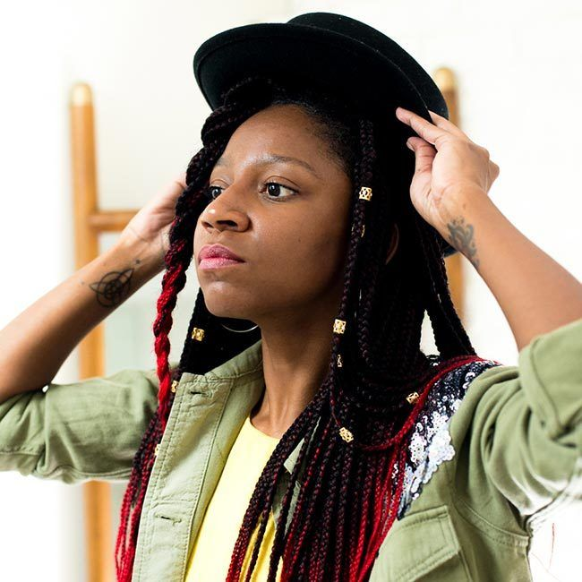 gerilyn hayes wears yellow dress and sequined military-style jacket, and puts black hat onto of ombre red box braids