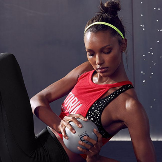 A brown skinned model with a workout-bun and fly-aways twists with an exercise ball