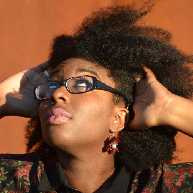 Editor April B runs her hands through a thick twistout and looks at the sky questioningly.