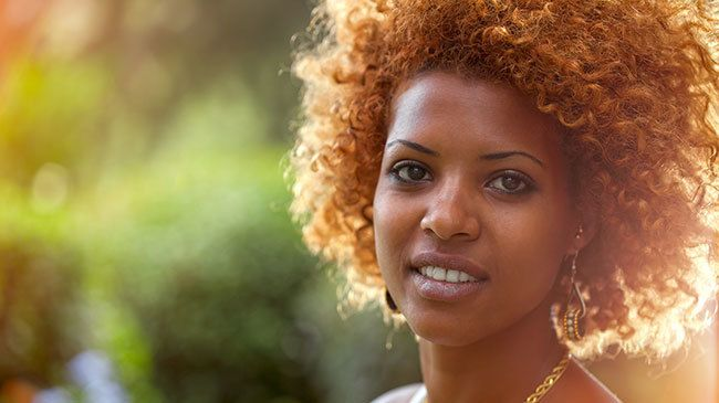 Smiling African woman in sunshine Outdoors from istock alexey_ds