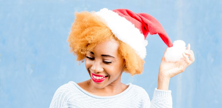 A black woman with a bright orange afro fluffs the pompom on her Santa hat