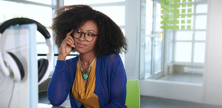 A black woman with glasses and a large twistout sits at her desk in a bright and very minimalist home office