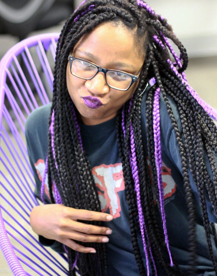 Editor Gerilyn Hayes scrunching her face at the camera in purple & black box braids and matching purple lipstick