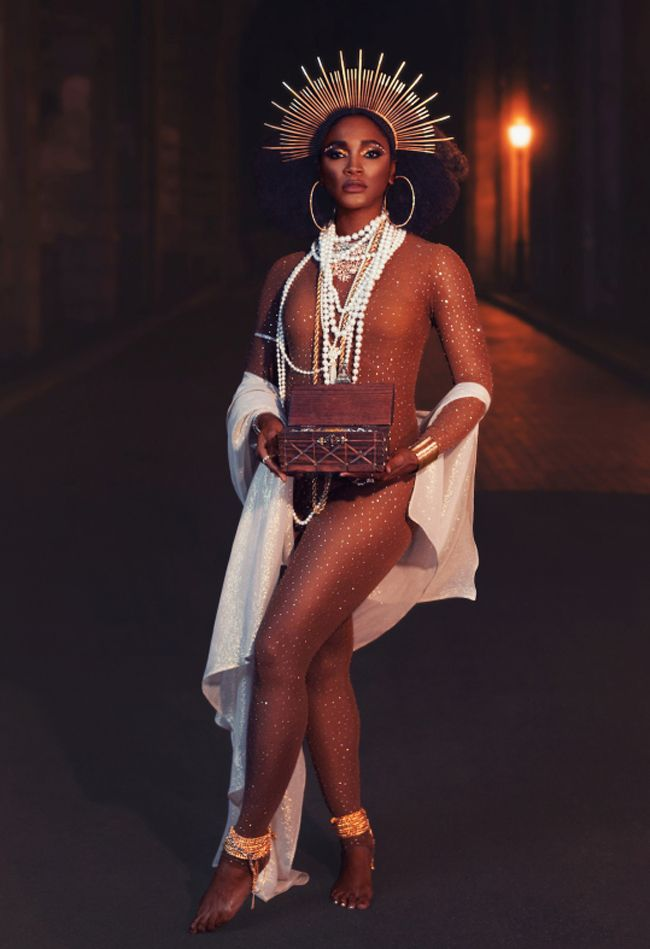 A black woman in a bedazzled body suit and halo-like crown holds a box of precious substances