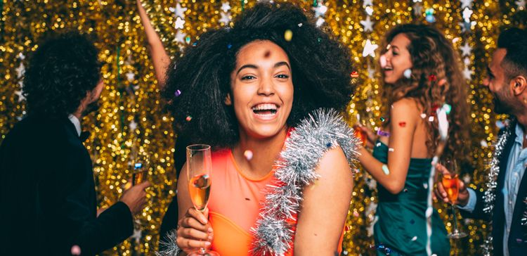 A smiling woman with big curly hair holds champagne with her friends as glitter falls