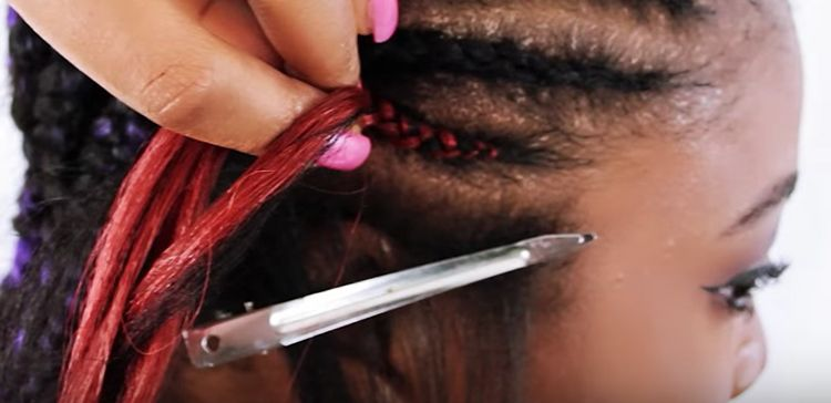 A close up of a black woman with pink nails tightly braiding her hair with feed in cornrows.