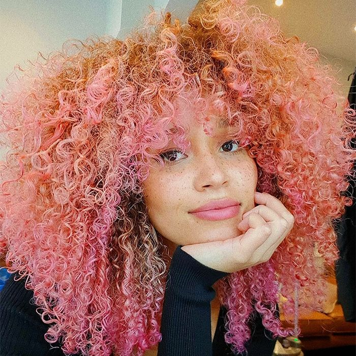 Woman with curly hair of multi colorful pink shades