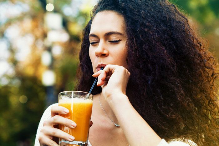 curly woman drinking juice