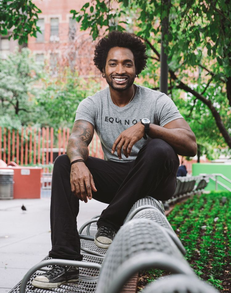 A well muscled black man with a full head of coily hair smiles from his seat on a row of park benches
