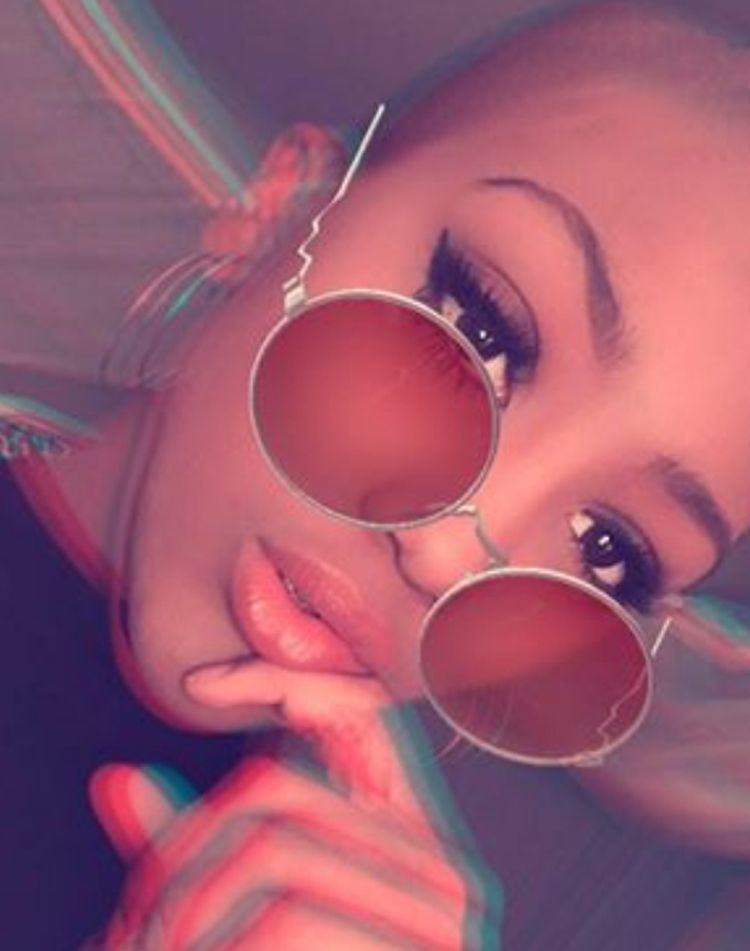 Lulu wearing round sunglasses and smoky makeup with a filter that distorts the image in the style of looking at a flat picture with 3d glasses