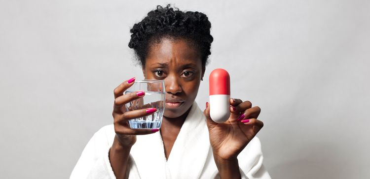 A black woman with beautiful deep skin holds a giant pill bigger than her hand and a glass of water with a quizzical look.