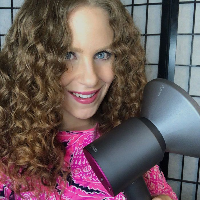 curly woman with dyson dryer