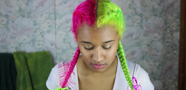 A girl with light caramel skin shows off her dyed neon green and pink hair in French braid pigtails