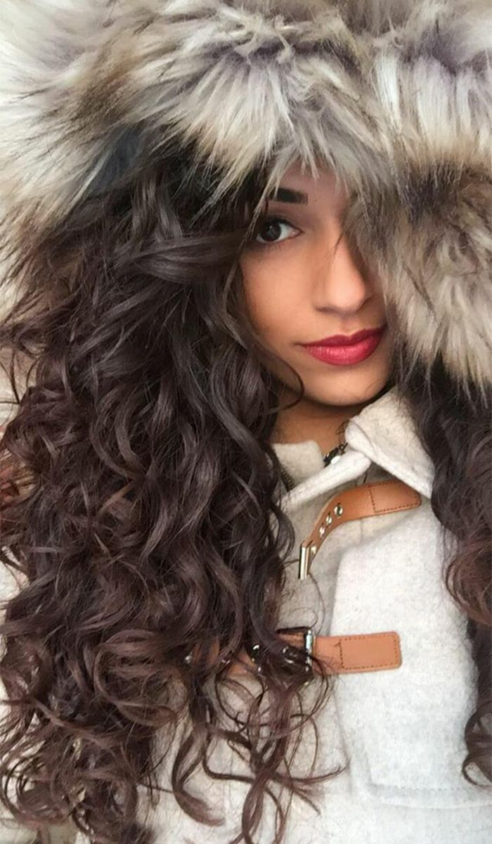 Woman with curly brown hair wearing a fur hooded jacket