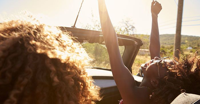 Young couple in an open top car, woman with arms raised Photo by monkeybusinessimages for iStock