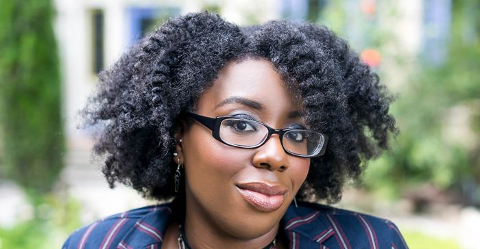Editor April B a black woman with glasses and a fluffy twist out sits and smiles.