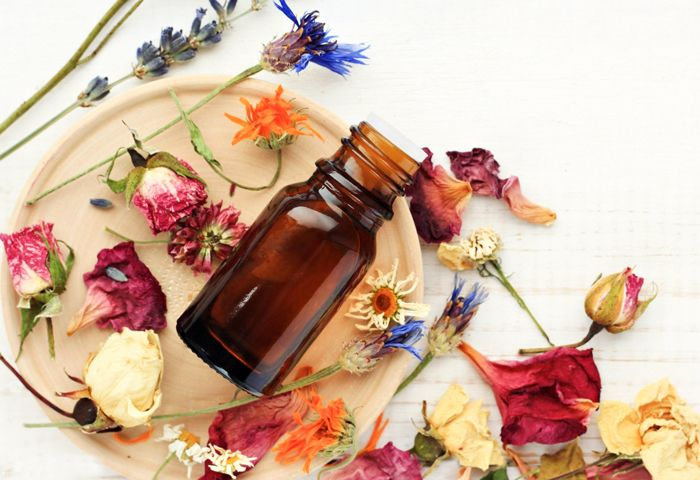 A small brown bottle of essential oil rests among various romantic looking dried flowers