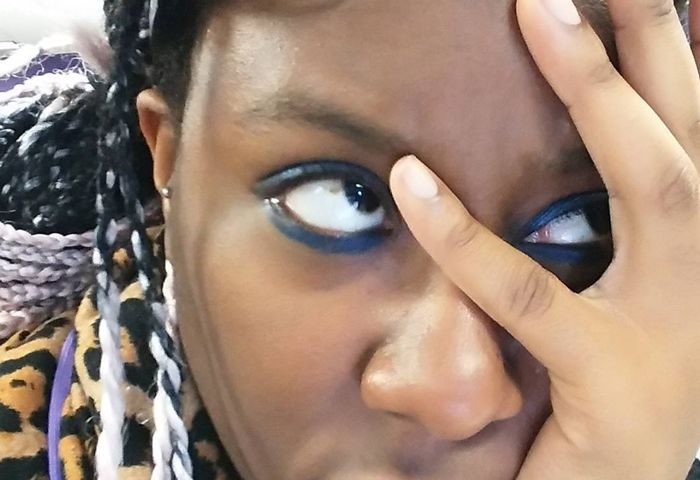 April B a black woman with braids and thick blue eyeliner, facepalms and rolls her eyes in annoyance