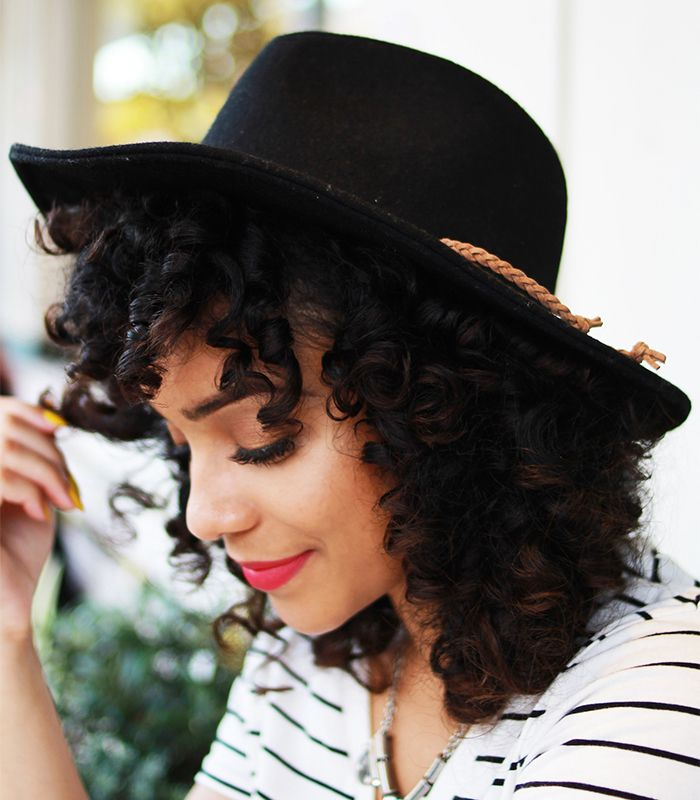 Woman with curly hair wearing a black hat