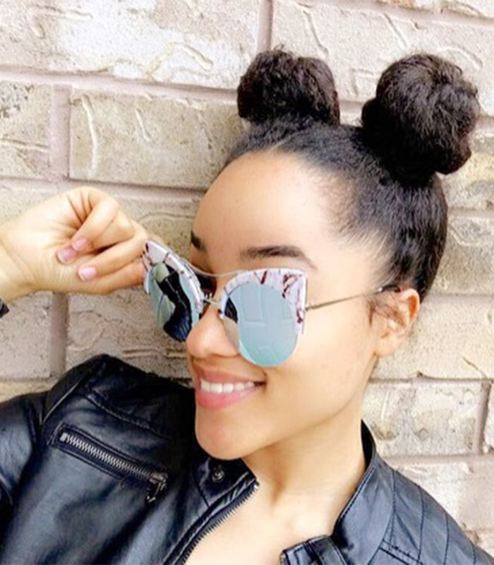 Woman wearinf sunglasses and her hair in two buns