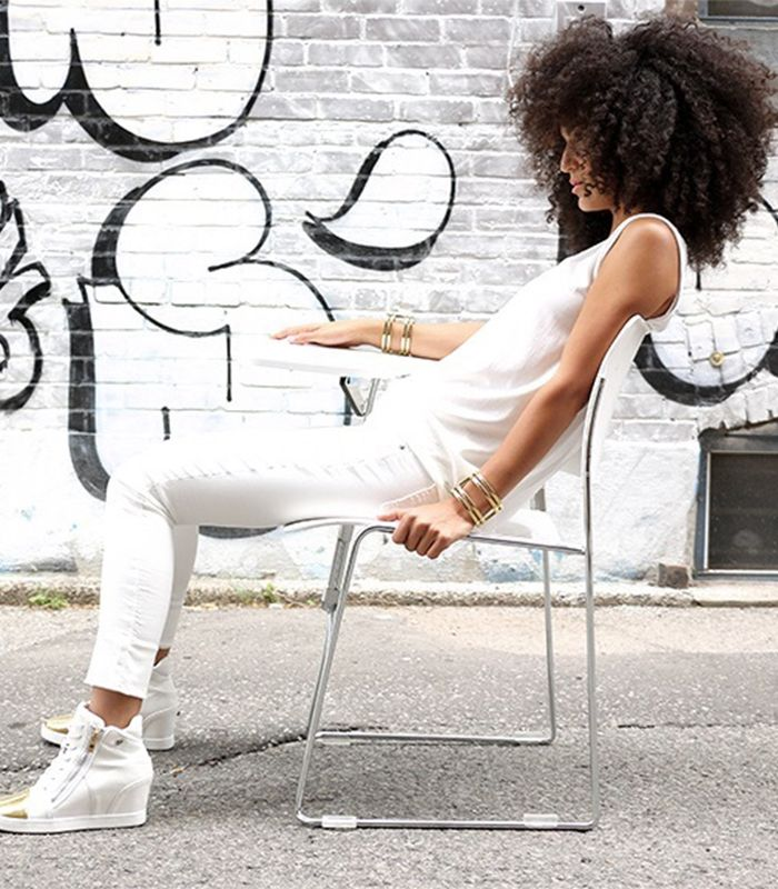 Woman sitting down in a desk wearing all white with an afro