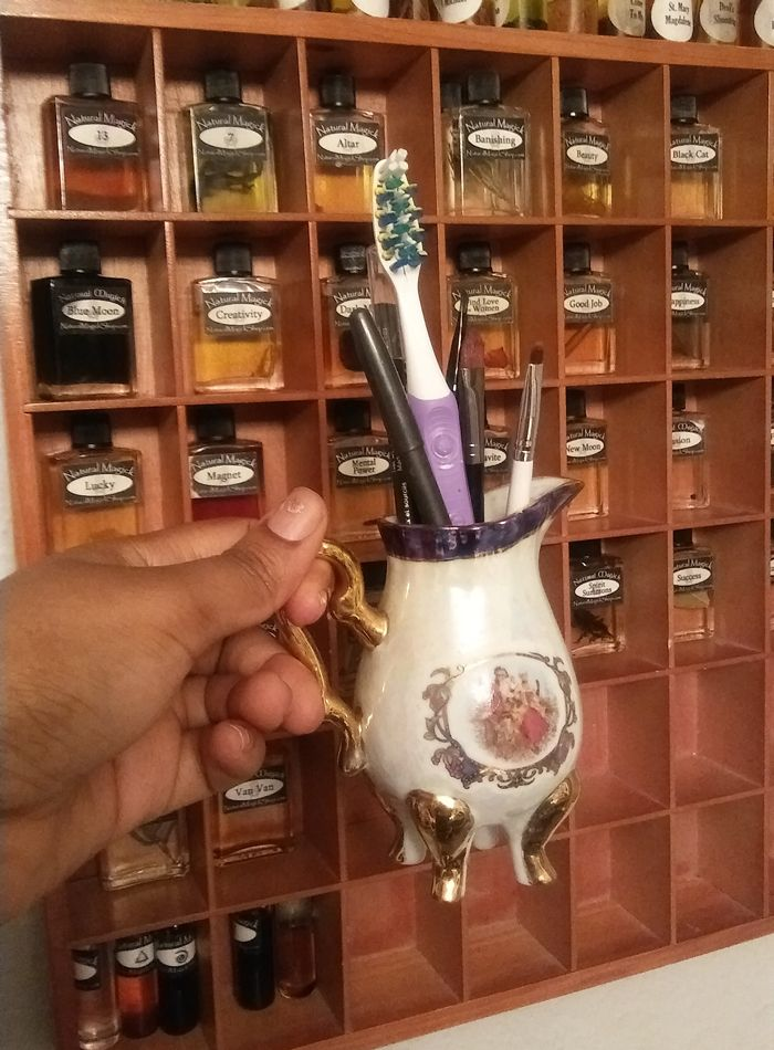 A cream pitcher with an 18th century French couple on it repurposed to hold my toothbrush and eyeliner