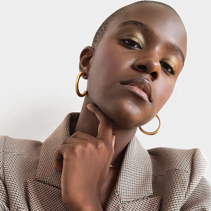 African-American wearing gold glossy eyeshadow and a plaid blazer