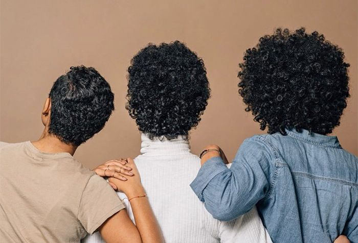 Three women with curly hair show off their hair texture standing arm and arm