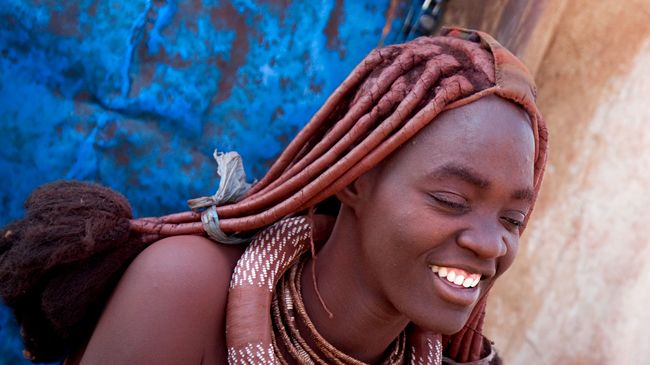 A Himba woman with long ochre covered locks flashes a bright smile