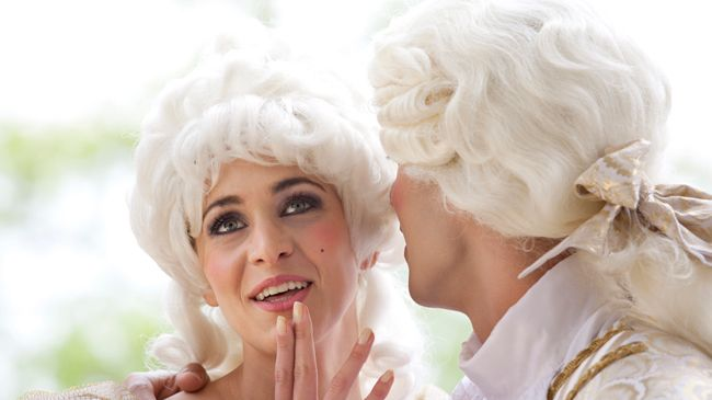 A pair of 18th century French aristocrats in powdered wigs share a secret.