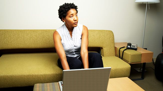 A black woman looks up from her laptop impatiently