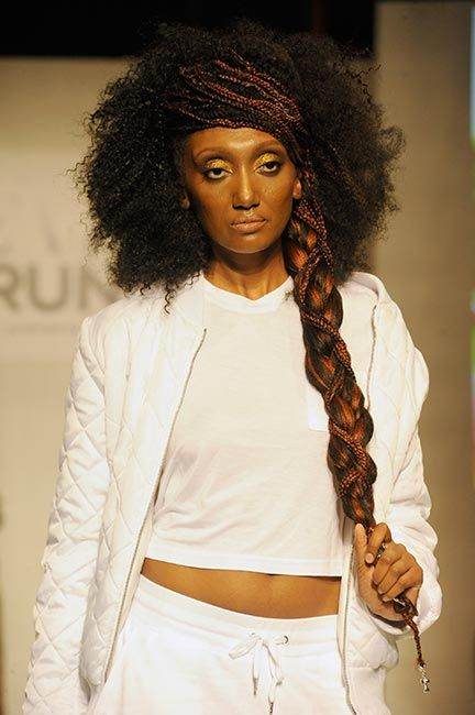 model wearing white outfit with braided hair style poses on runway