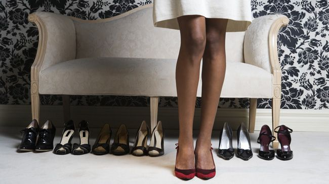 A black woman in red heels stands in front of several pairs of black pumps