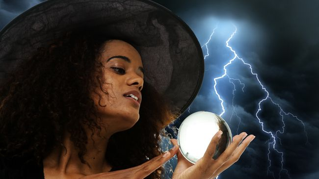 An Afro-Latina witch with lots of brown curly hair gazes into her crystal ball amidst a lightning storm
