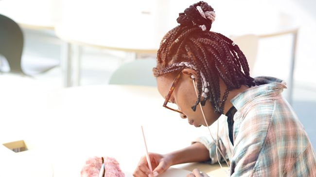 A young black woman with short multicolored box braids takes some notes with a pad and pen
