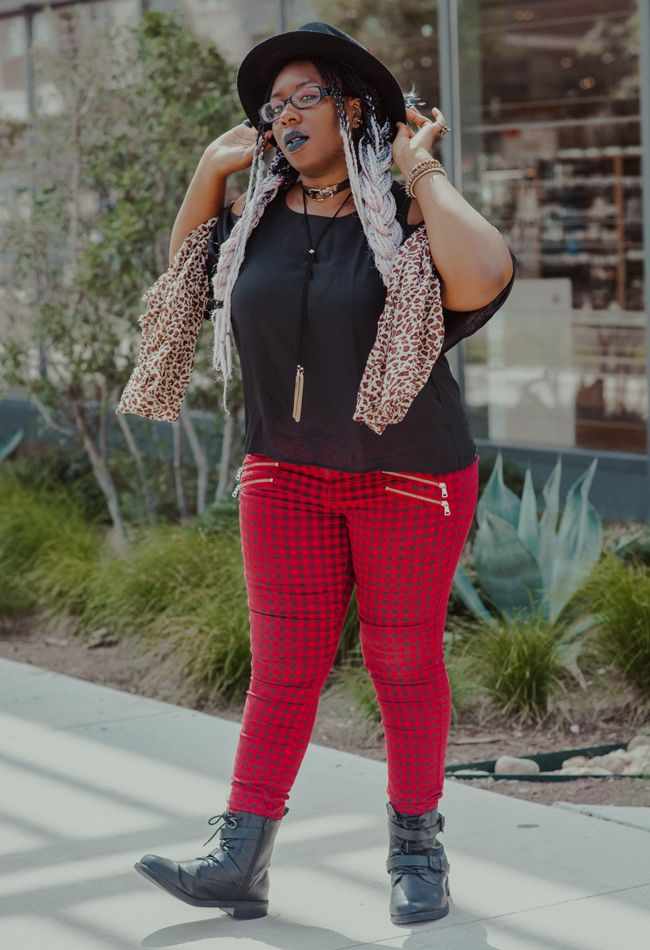 Editor April shows off in a full body shot showing fitted red plaid pants, flowy black top, leopard print scarf, and black buckled boots