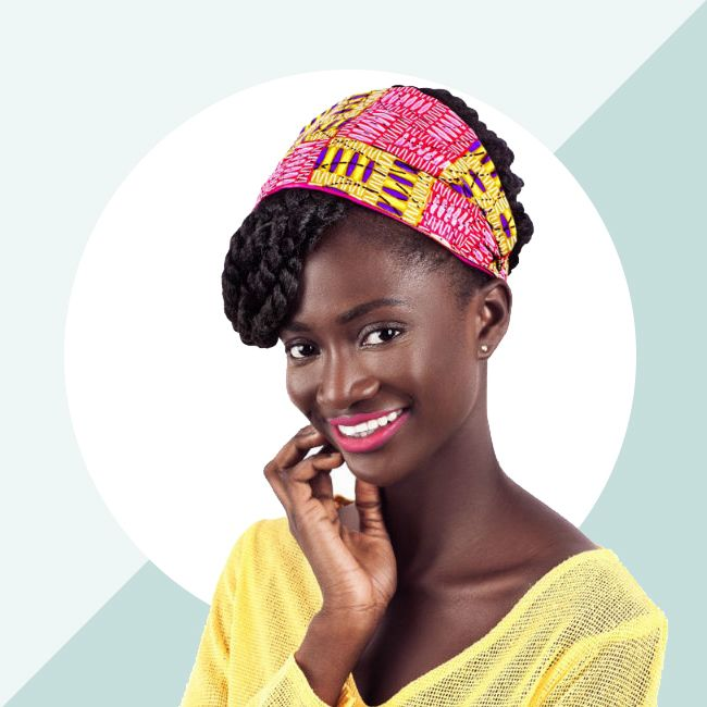 A smiling deep skinned model shows off a bright smile and the Loza Tam Pink (multicolored print) headband