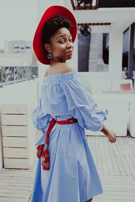 African-American woman is dressed in a blue and white striped dress wears red wide-brimmed hat and black boots.