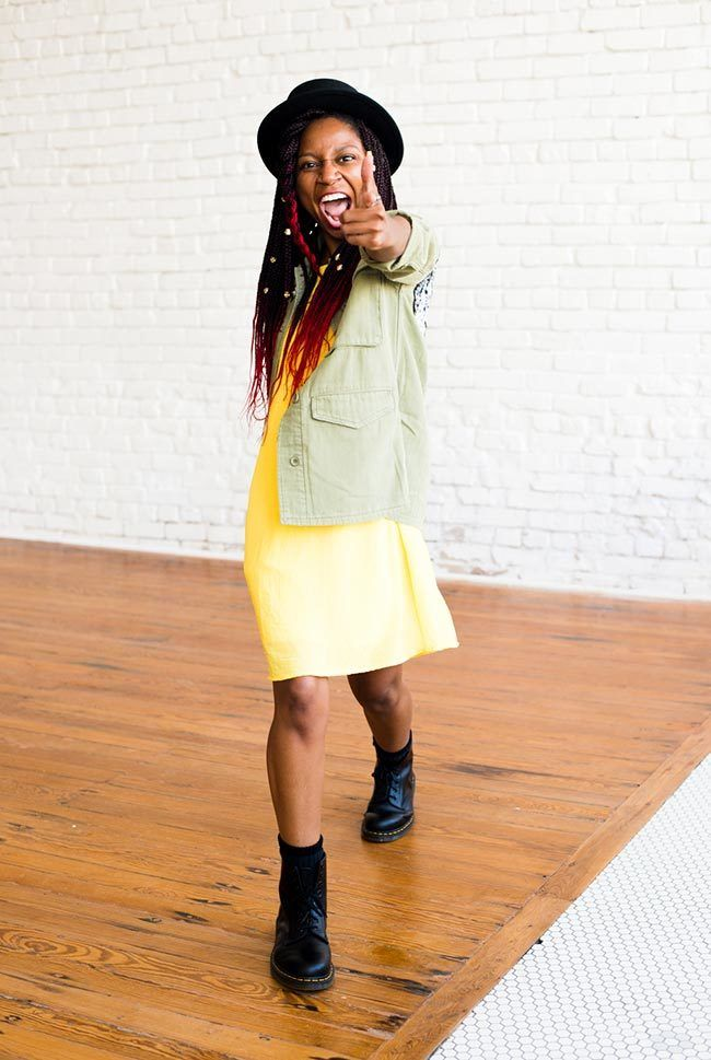 gerilyn hayes points at camera while wearing a yellow dress, sequined military-style jacket, black Dr Marten boots, and a black hat onto of ombre red box braids