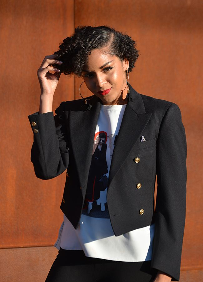A woman with short curly hair wearing a blazer
