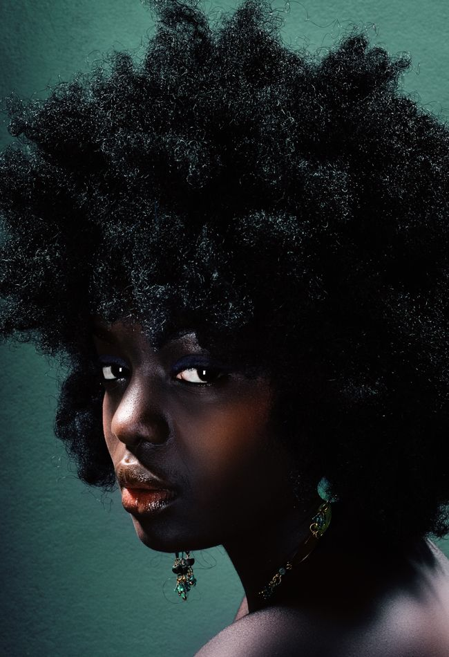 A deep skinned black woman with a large afro and dark sunken eyes stares at us hauntingly