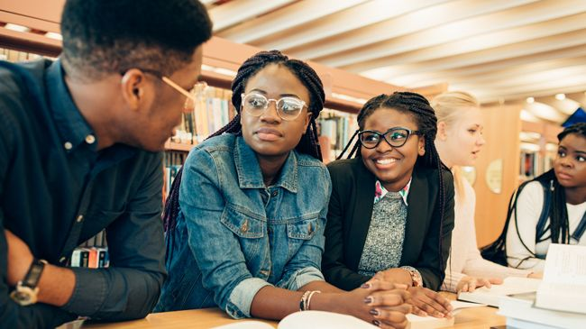 Five students, three of whom are black women with similar long pulled back braids regarding their other classmates, a fair white woman and a bespectacled black man