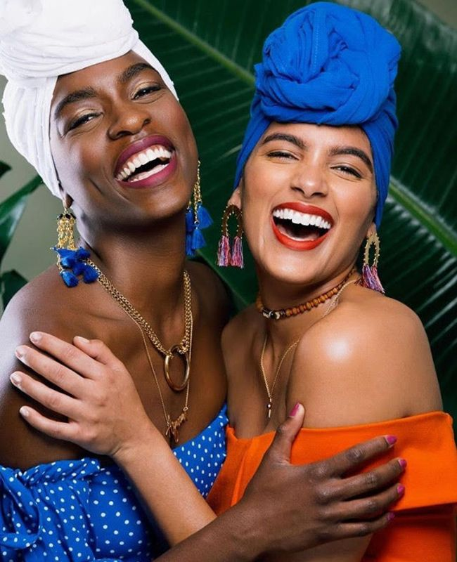Women laughing and hugging wearing headwraps
