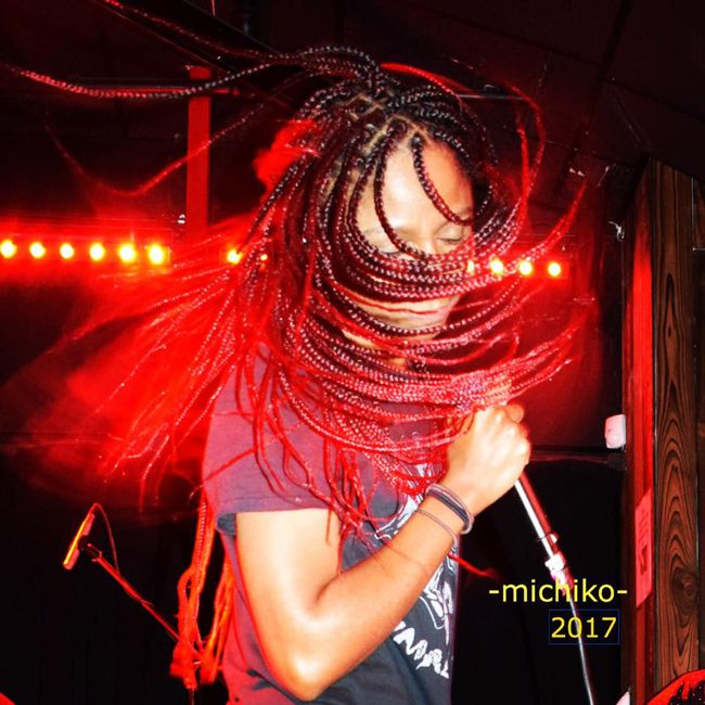 Gerilyn on stage whipping red and black braids around with her band Sugarpill.