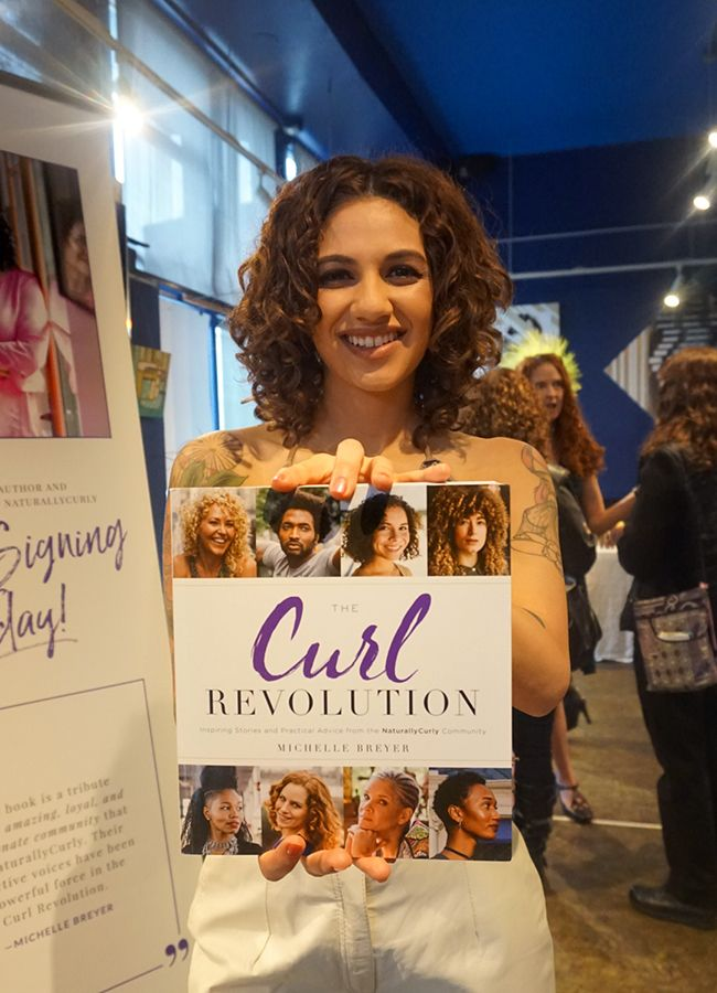 curly girl holding the curl revolution book