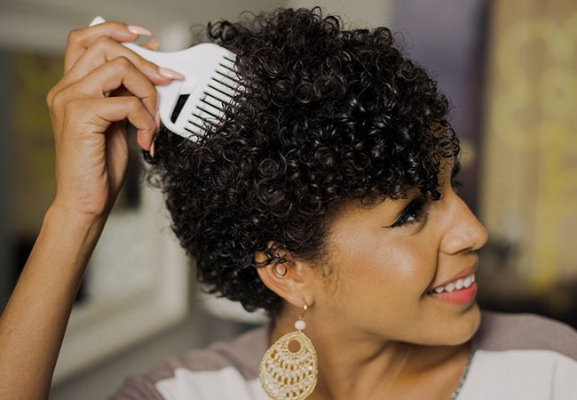 Woman using a pick for her curly hair