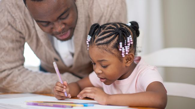 A black father with close cropped hair leans in to help his daughter in elaborate braids and beads with her homework