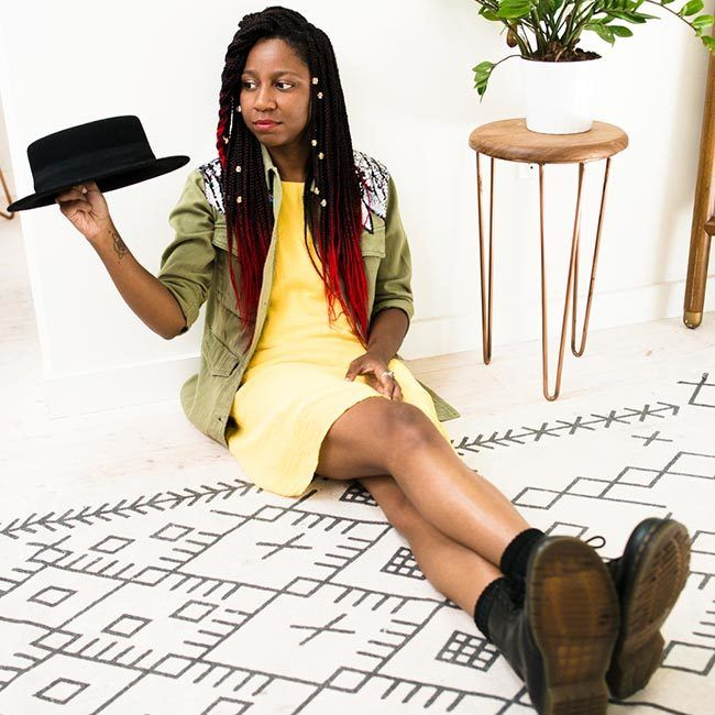 gerilyn hayes sits on wood floor and patterned carpet, and holds black hat in right hand